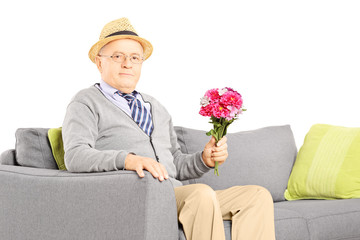Senior gentleman sitting on a sofa and holding flowers