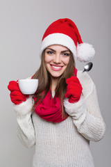 Cute young woman with Santa hat enjoying coffee