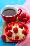 Fresh raspberries on the curd and tea. Selective focus