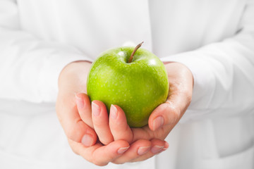 green apple in hands, white background