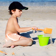 Little boy with hat playing on beach