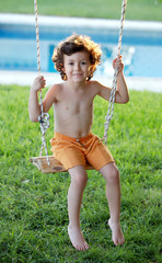 Happy little boy with curly hair sitting on a swing