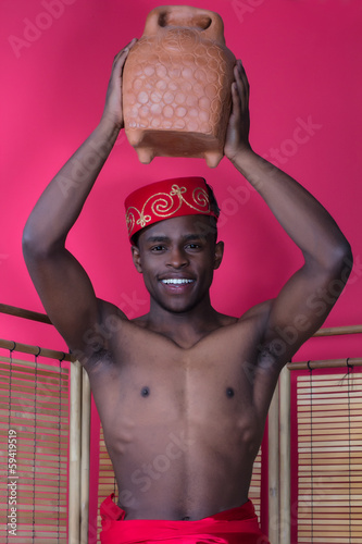Black man posing near a reed screen