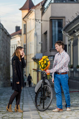 young woman surprised by her date who brings flowers