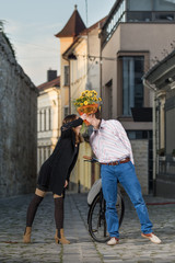 young woman and man kiss behind a bouquet of flowers
