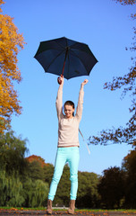 sweet girl jumping with umbrella in autumnal park