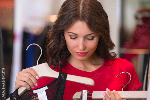 Woman shopping in an clothes store trying on new clothes
