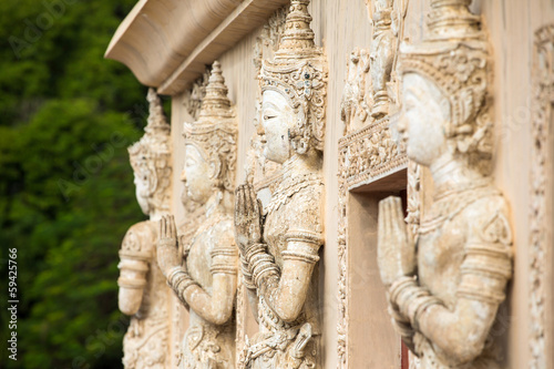 Stone praying women carvings on the wall of the temple in Thaila