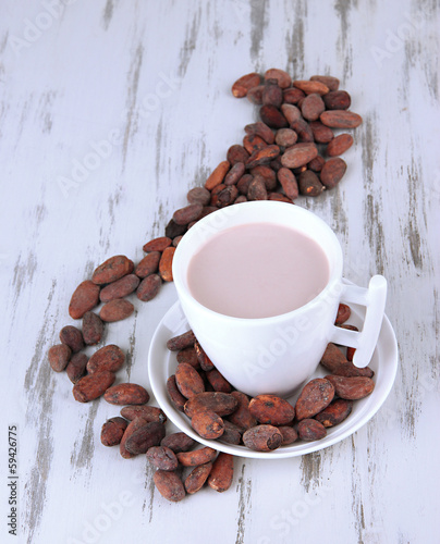 Cocoa drink and cocoa beans on wooden background