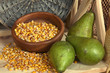 Bowl of corns with pears on shelf on wicker background