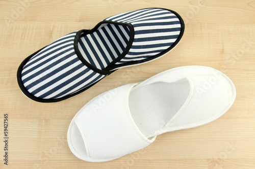 Striped and white slippers on wooden background