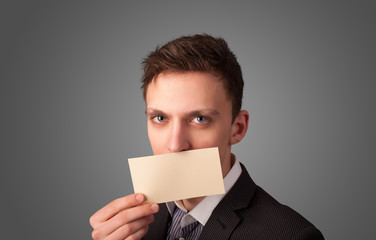 Businessman holding white card at front of her lips with copy sp