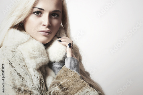 Beautiful blond woman in Fur Coat.Winter fashion.text here