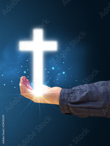 Glowing cross in the hand of a woman