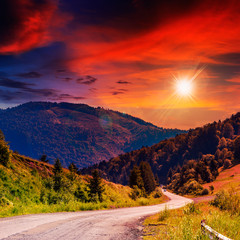 mountain road near the coniferous forest with cloudy sunset sky