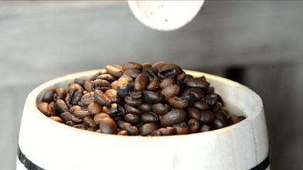Holzloz taucht in Fass mit Arabica Kaffeebohnen