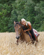 Сowgirl rides through a wheat field