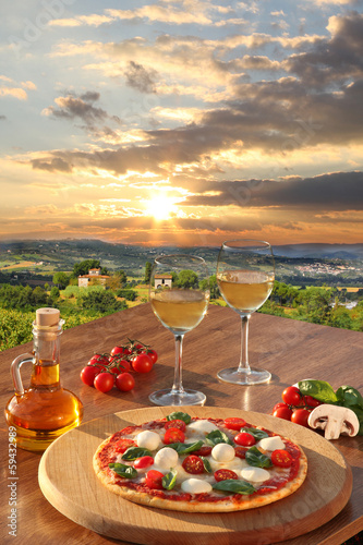 Italian pizza and glasses of white wine in Chianti, Italy