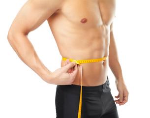Muscular young man measuring waist