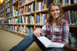 Happy pretty student sitting on library floor reading book