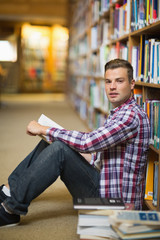 Handsome student sitting on library floor reading