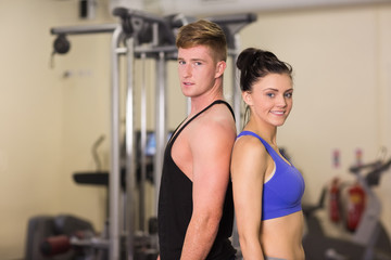 Sporty woman and man standing back to back in the gym