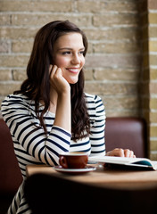 Woman With Hand On Chin Looking Away In Cafeteria