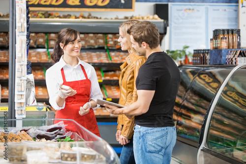 Leinwandbild Motiv Saleswoman Assisting Couple In Buying Meat