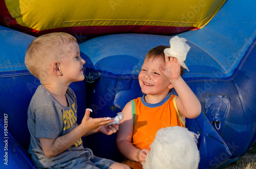 Two boys laughing as they share cotton candy