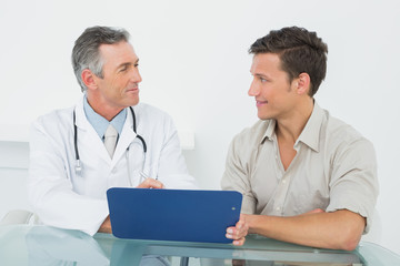 Doctor discussing reports with patient in office