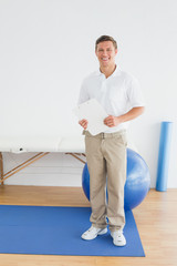 Smiling male trainer with clipboard in gym at hospital