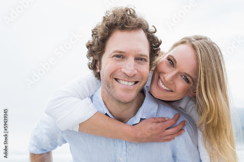 Man piggybacking woman at beach