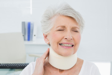 Senior woman wearing cervical collar with eyes closed