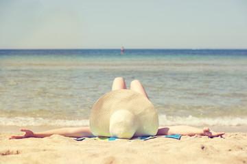frau liegt entspannt am strand