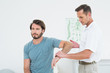 Male physiotherapist examining a young man's arm