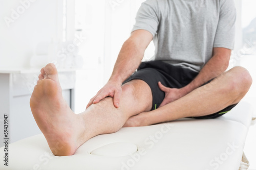 Low section of a man with hands on a painful leg