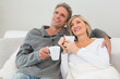 Relaxed couple with coffee cups in living room