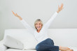 Cheerful woman sitting on sofa with arms outstretched at home