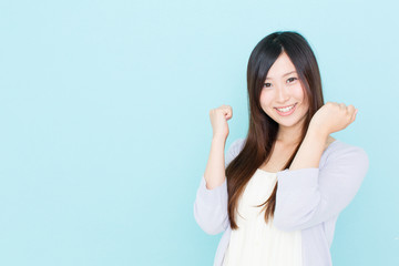 young asian woman cheering on blue background