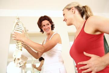 Physiotherapeutin erklärt Patientin den Brustkorb