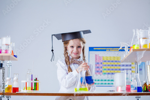 Smiling little girl posing in graduate hat at lab