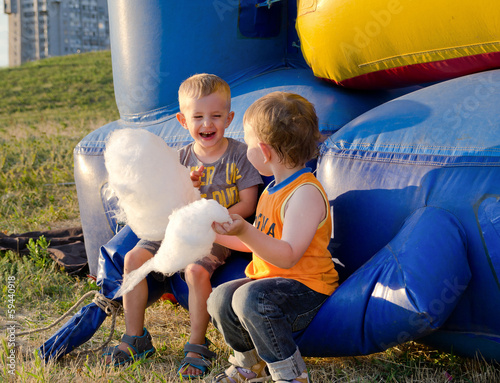 Two little boys eating candy floss
