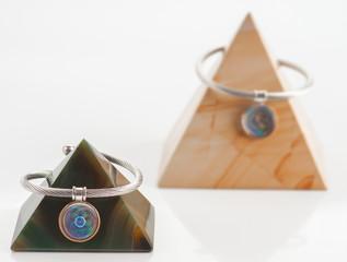 Spiral steel bracelets engraved on marble pyramids