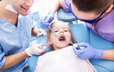 Girl having teeth examined at dentists
