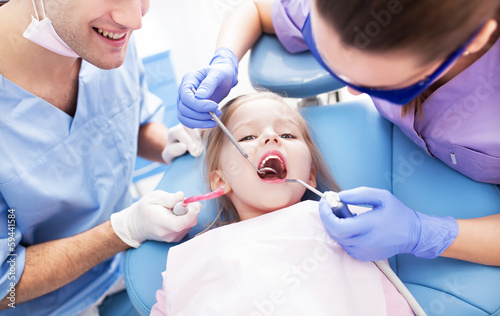 Girl having teeth examined at dentists