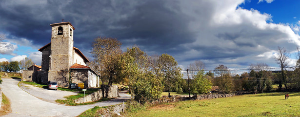 panorama of rural village with stormy clouds. Gujuli, Alava.