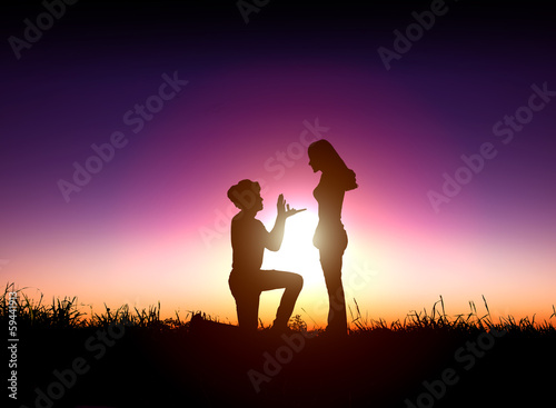 man proposes a woman to marry with sunrise background