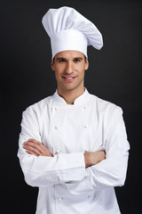 Chef cook against dark background smiling with hat