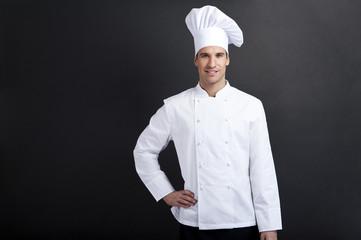Smiling cook against dark background smiling at camera