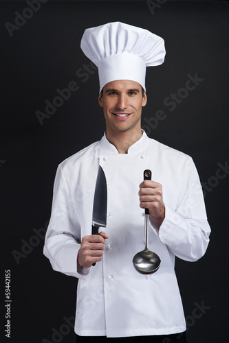 Chef cook against dark background smiling with hat holdinf spoon